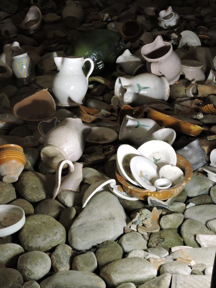 Porozrzucane naczynia. Przyklad jak dawniej wyrzucano odpady do rzeki pod szpitalem